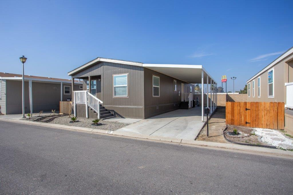 double wide brown mobile home with indoor car park
